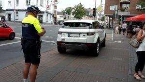 Polizist in Fahrradkleidung schreibt Falschparker auf, der Radweg an Kreuzung zuparkt