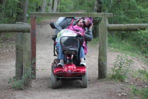 Lächelnde Frau mit Sonnen auf Elektro-Rollstuhl beugt sich stark zur Seite, um unter einer Durchfahrsperre auf einem Waldweg durchzufahren.